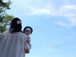 曇り青空の前に立っている人の写真・画像素材[1864614]