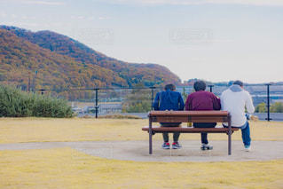 水の体の横にあるベンチに座っている人の写真・画像素材[1726034]