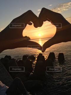 夕焼けの前に立つ人々のグループの写真・画像素材[2280601]