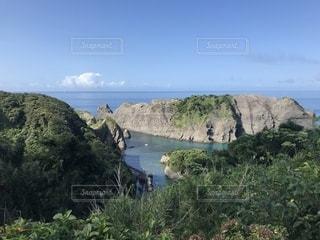 近くに水の体の横にある丘の中腹のアップの写真・画像素材[1719860]