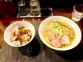 近くのテーブルの上の皿の上に食べ物のボウルの写真・画像素材[1760293]