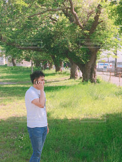 木の前に立っている人の写真・画像素材[2138561]