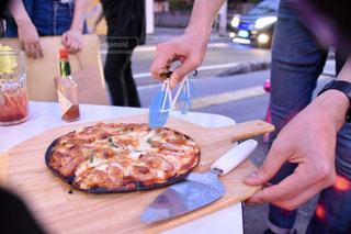 ピザを食べるテーブルに座っている人々のグループの写真・画像素材[2307113]
