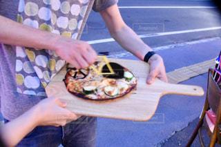 ピザを食べるテーブルに座っている女性の写真・画像素材[2307151]
