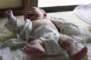 布団の上で泣いている赤ちゃんの写真・画像素材[1742882]