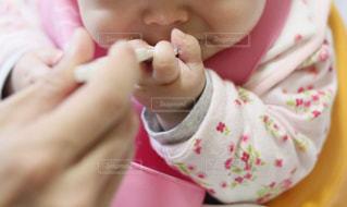 離乳食を口に運ぶ赤ちゃんの写真・画像素材[1746050]