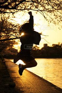 夕暮れにジャンプして遊ぶ女の子の写真・画像素材[1761106]