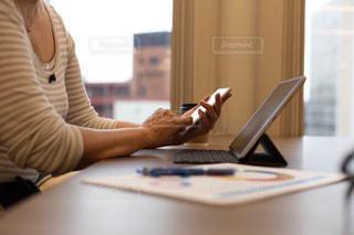 ノートパソコンを使ってテーブルに座っている女性の写真・画像素材[2320101]
