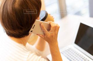 ラップトップコンピュータを使ってテーブルに座っている女性の写真・画像素材[2336631]
