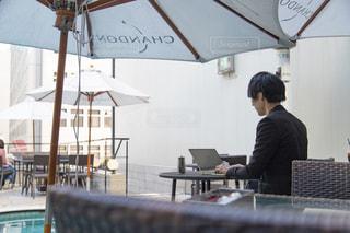傘を持ってテーブルに座っている男の写真・画像素材[2404143]