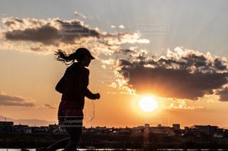 夕焼けの前に立っている女性の写真・画像素材[2419716]