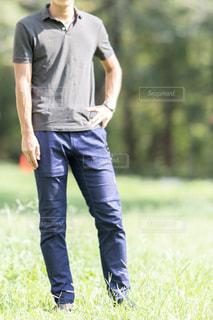 草に覆われた野原の上に立っている男の写真・画像素材[2419738]