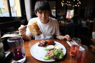 食べ物を食べるテーブルに座っている人の写真・画像素材[2426667]