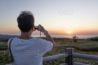 フェンスの前に立っている男の写真・画像素材[2496287]