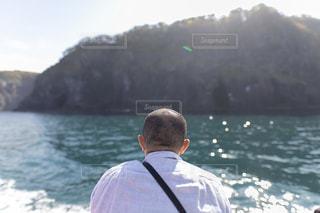 水域の隣に立っている男の写真・画像素材[2496297]