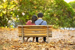 公園のベンチに座っている人の写真・画像素材[2724721]