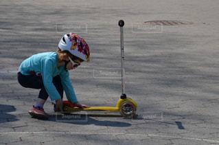 スケートボードに乗って道路の脇に乗っている少年の写真・画像素材[2727177]