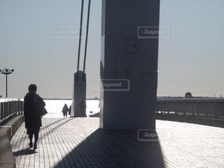 水域に架かる橋を渡る男の写真・画像素材[2879376]