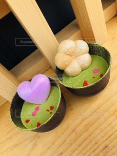 木製のテーブルの上に座っているドーナツの写真・画像素材[2127301]