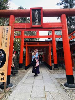 伏見稲荷大社を背景に赤いベンチの前に立つ人々のグループの写真・画像素材[3034081]