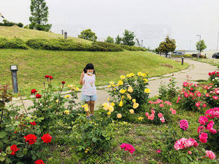 花の庭の前に立っている人の写真・画像素材[3211321]
