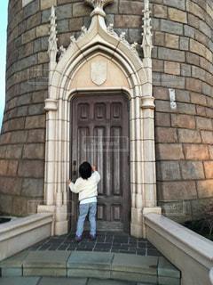 れんが造りの建物の前に立っている人の像の写真・画像素材[2098970]