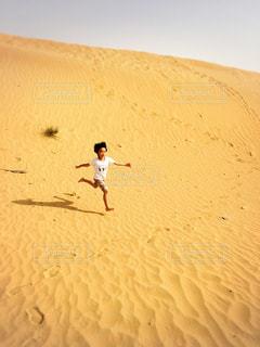 砂漠を駆け下りる少年の写真・画像素材[1770032]