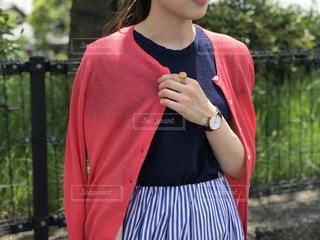 フェンスの前に立っている赤いドレスを着ている人の写真・画像素材[1207945]