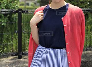 フェンスの前に赤いシャツ立って身に着けている人の写真・画像素材[1207946]