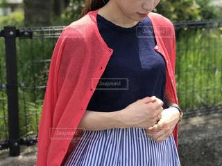 フェンスの前に立っている赤いドレスを着ている男の子の写真・画像素材[1207947]