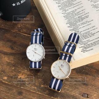 木製のテーブルの上に座っている時計の写真・画像素材[2181976]