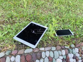 草の上のiPadとスマホの写真・画像素材[2152924]