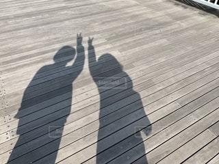 ピースサインをする人の影の写真・画像素材[2186390]