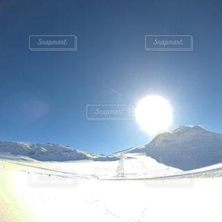 雪に覆われた山の頂上に立っている男の写真・画像素材[1774017]