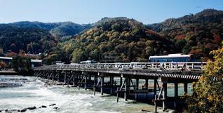 背景の山が付いている水の体の上の橋の写真・画像素材[1776655]