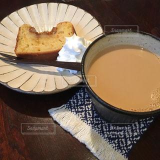 コーヒー カップの横にある皿の上のケーキの一部の写真・画像素材[1780734]