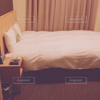 部屋に座っている大きな白いベッドの写真・画像素材[1781682]