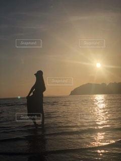 バック グラウンドで夕焼けのビーチに立っている人の写真・画像素材[1785775]