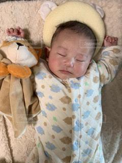 狐のぬいぐるみの横に眠っている赤ちゃんの写真・画像素材[1845697]