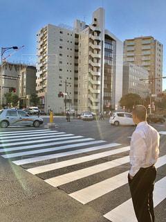 遠くの警官と事故現場を眺める男性の後ろ姿の写真・画像素材[2602036]