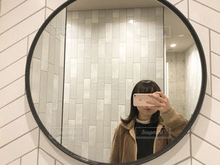 カメラにポーズ鏡の前に立っている女性の写真・画像素材[1799949]