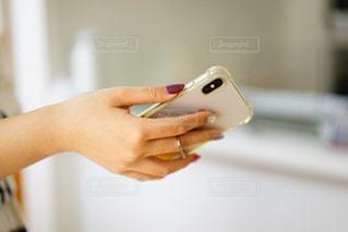 スマホを持つ女性の手元の写真・画像素材[2010875]