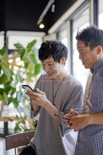 スマホを見ながら会話する男性達の写真・画像素材[2295902]