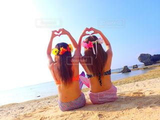 砂浜に座っている女の子の写真・画像素材[1800706]