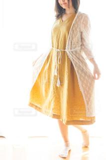 黄色のワンピースと白いカーディガンをカーディガンを着た女性の写真・画像素材[2389066]