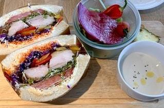 木製のテーブルの上に座っているサンドイッチの写真・画像素材[3471160]