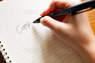 コピーライティングを考えるコピーライターの手とペンと紙の写真・画像素材[3866641]
