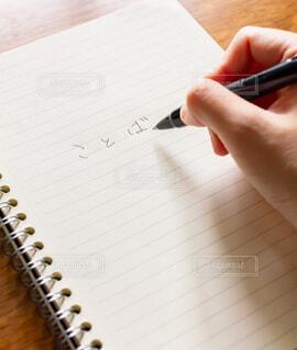 ノートにペンを手で持って書いた言葉の写真・画像素材[3866660]