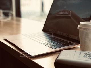 テーブルの上に座っている開いているラップトップ コンピューターの写真・画像素材[1807958]