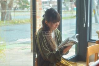 ウィンドウの前に座っている女性の写真・画像素材[1862975]